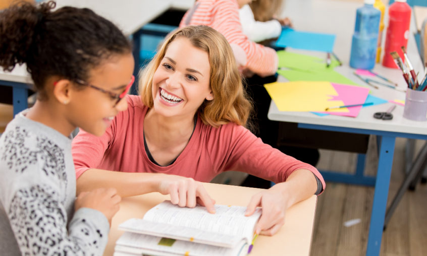 A substitute teacher works with a student